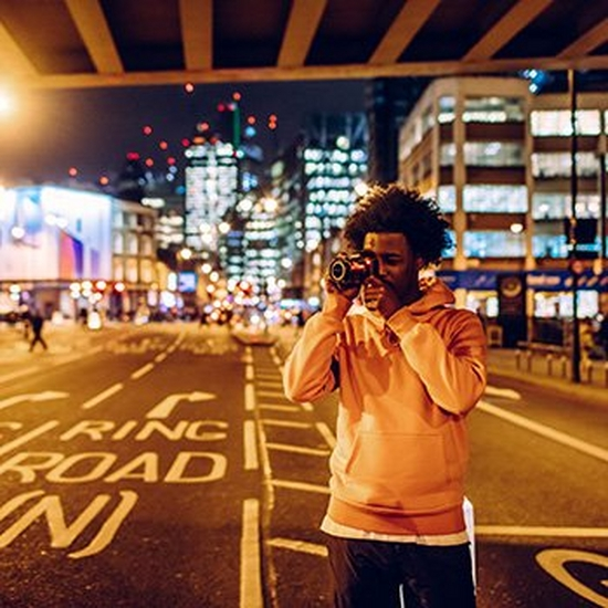 A man stands under a city centre bridge beside a road to take a photo with a Canon camera.