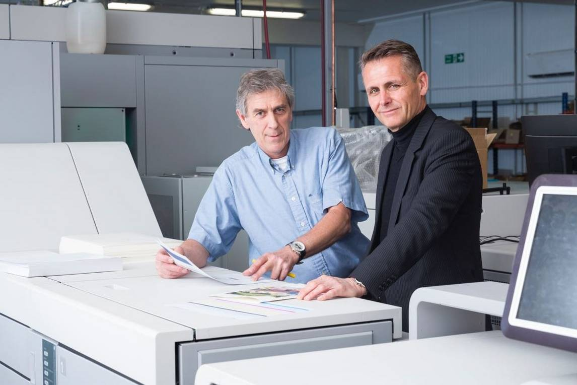 Two men examine personalised book printing pages on top of printing press