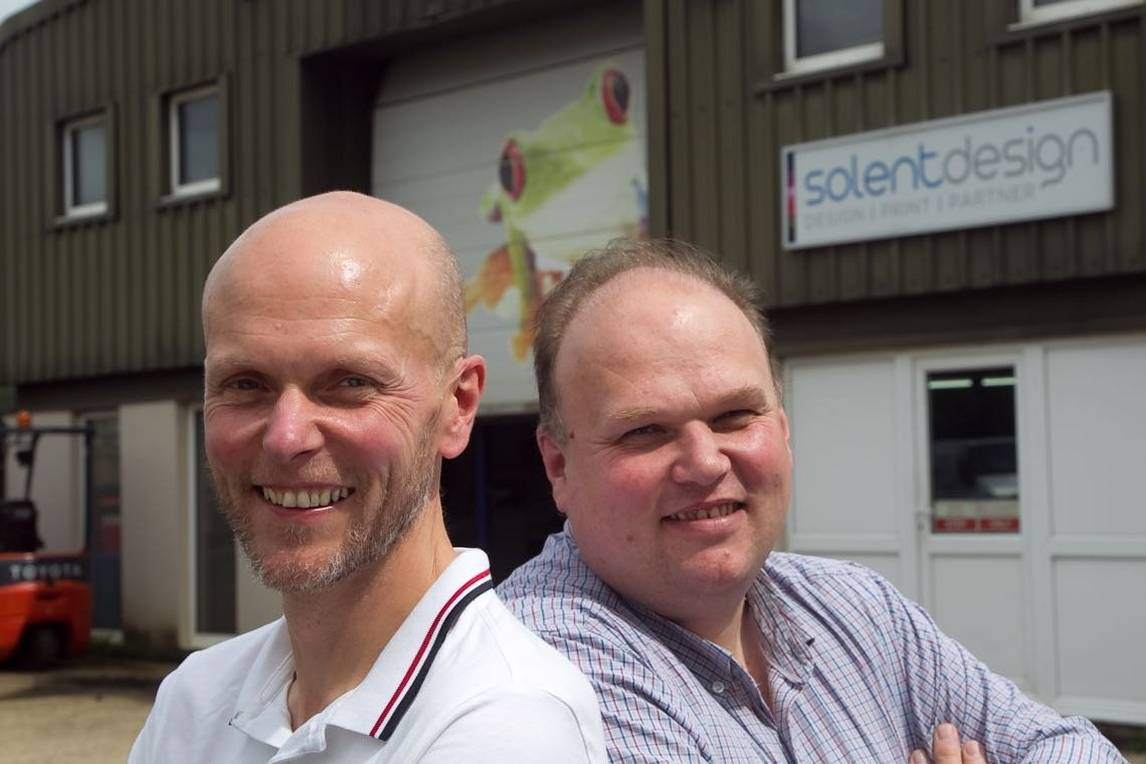 Two men stand back to back in front of Solent warehouse