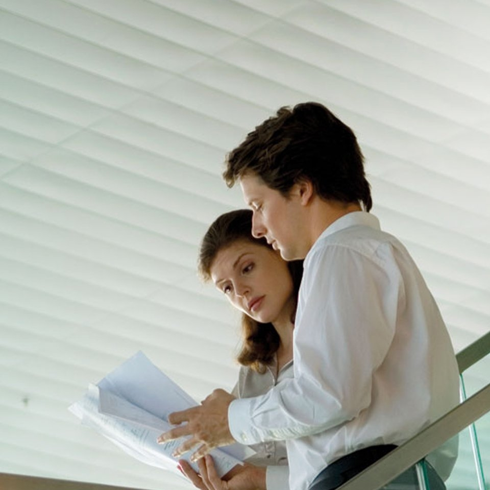 Image showing two colleagues analysing some worksheets
