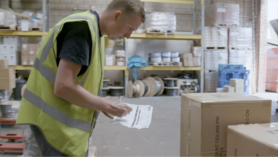 Man in high visibility vest takes stock of boxes in electrical wholesaler warehouse