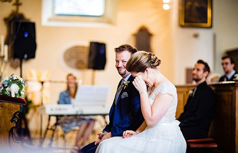 A bride and groom sat in a church, the bride is wiping her eyes.