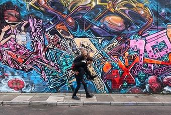 Women piggyback on man streetart background