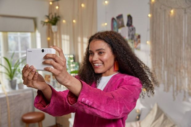 A girl taking a selfie with Canon Zoemini C in her room.