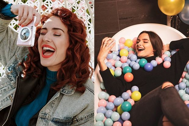 2 young women - one taking a photo with Canon Zoemini S, one taking a selfie in a bathtub filled with colourful balls.
