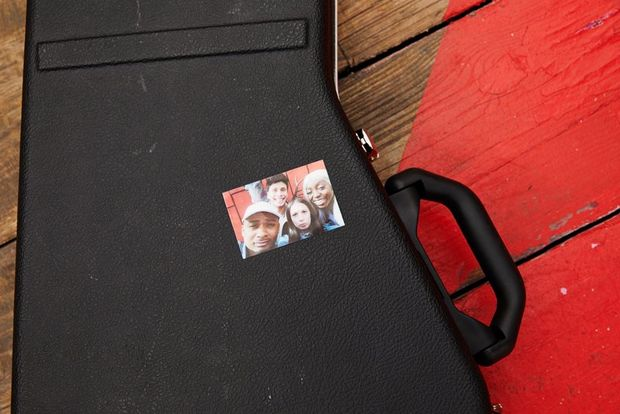 Guitar case with a picture of 4 young people stuck to it.