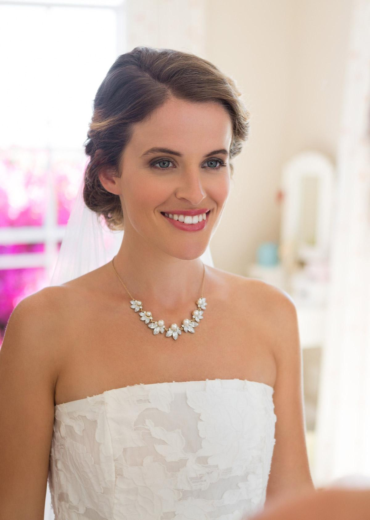 Close up image of a bride wearing a statement diamond necklace and strapless wedding dress
