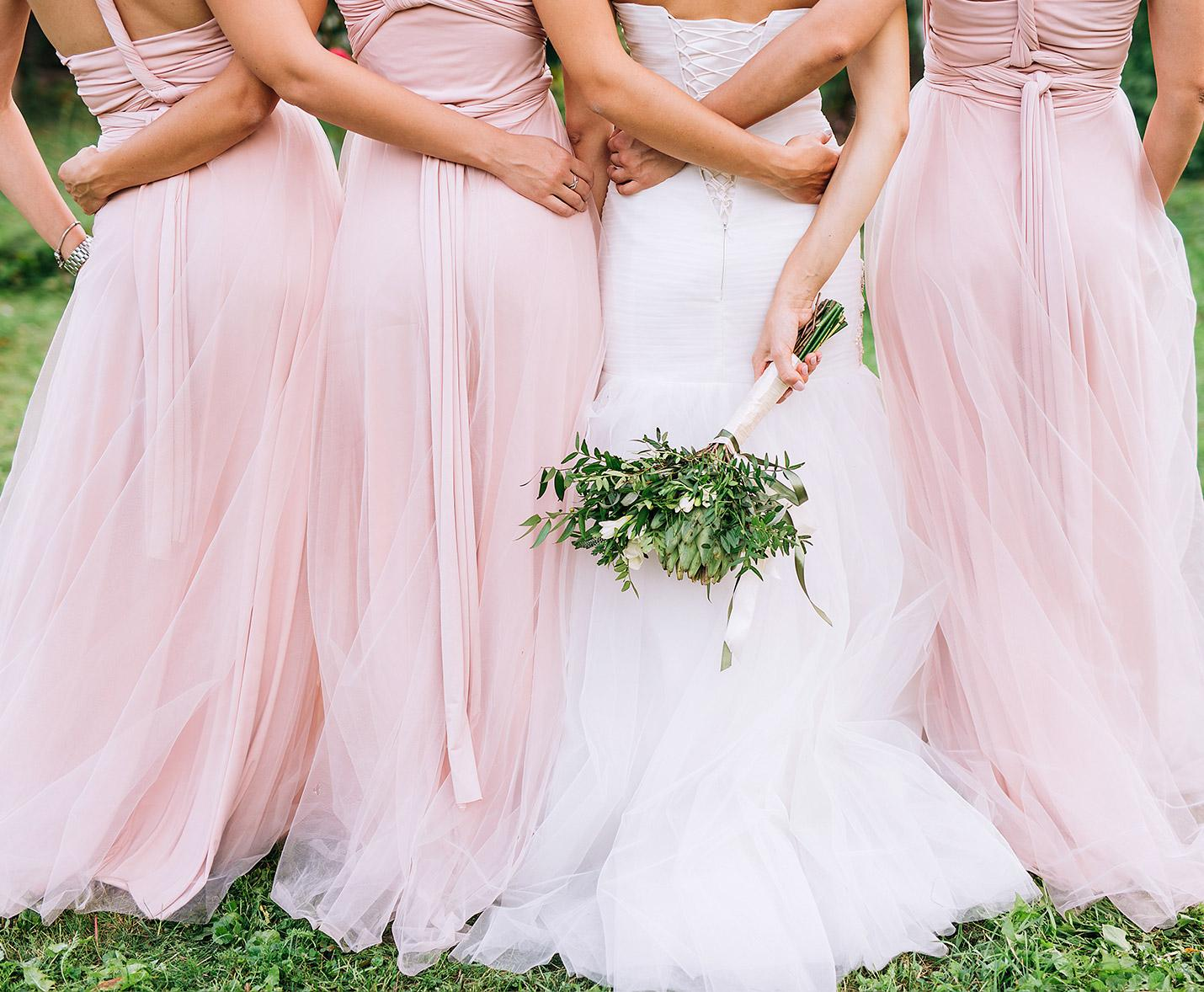 A bride and her bridesmaid with their backs to the camers