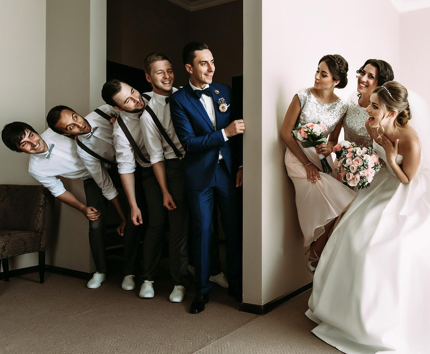 Groom and bridal party leaning past a wall