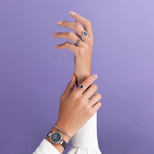 Elegant hands wearing sapphire rings, diamond tennis bracelet and navy watch
