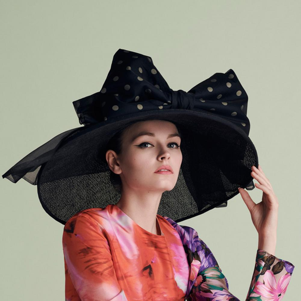 Model in a black Monique Lee hat
