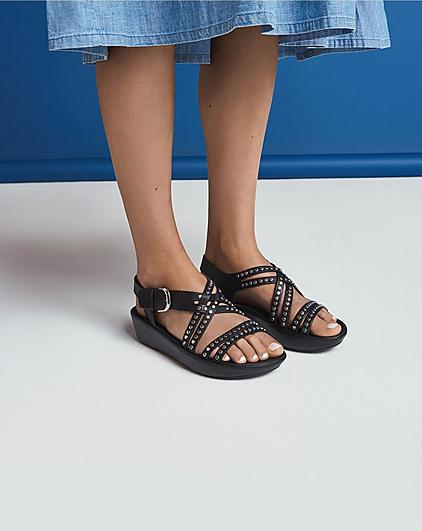 Woman wearing black studded sandals on a blue background.