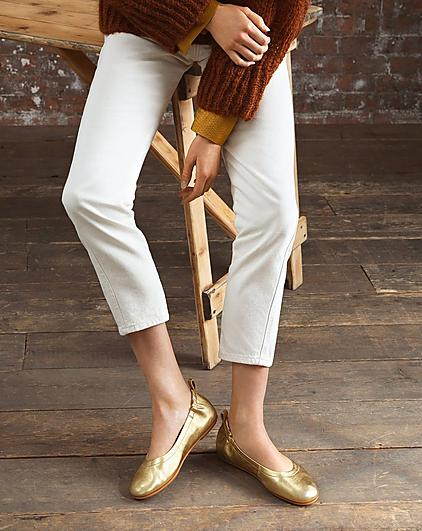A woman wearing white trousers and gold ballerina shoes.