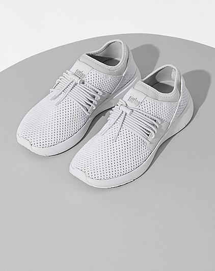 A pair of white sneakers on a light grey background.