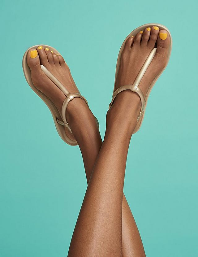 Women modelling Iqushion gold flip-flops