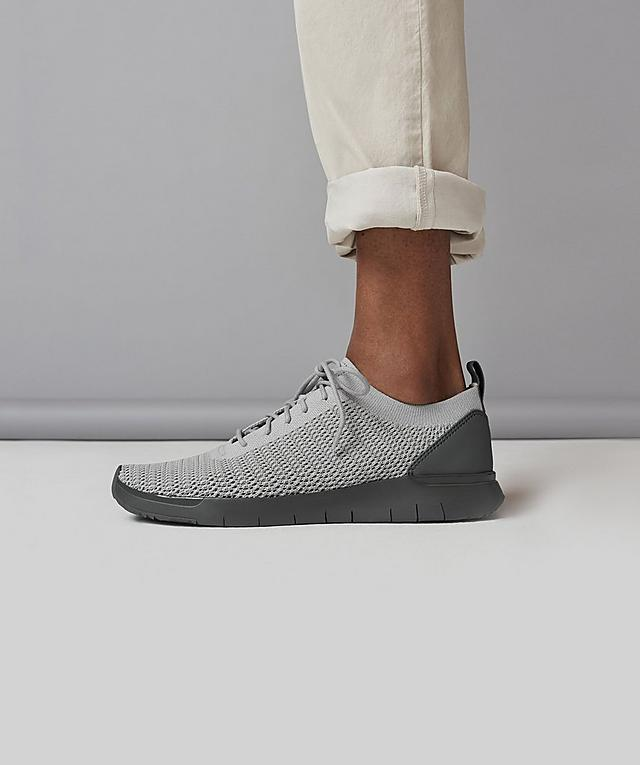 Men's Knitted Light Grey Sneakers with a dark Grey base. Modelled with Beige trousers.