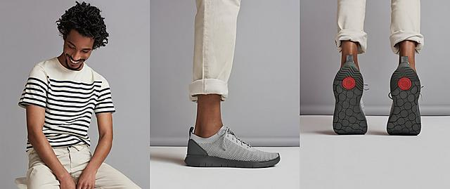 Men's Knitted Light Grey Sneakers with a dark Grey base. Modelled with Beige trousers and a striped T-shirt.