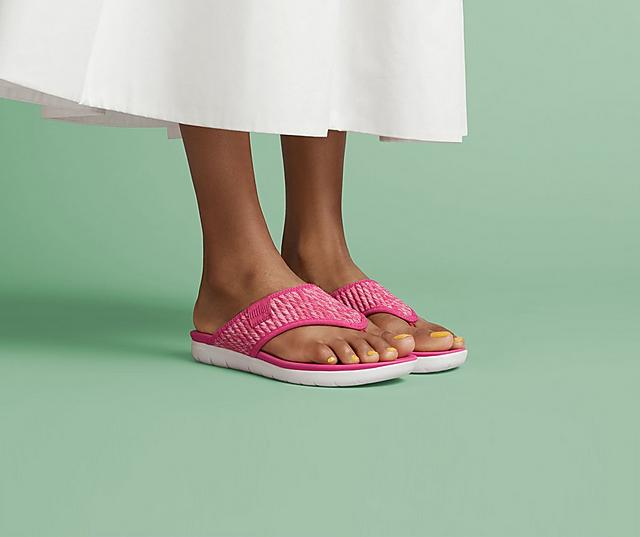 A woman modelling pink sandals in front of a green background.