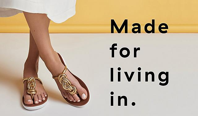 Women wearing Twiss Gold Leather Toe-post sandals.  featuring two large twisted braid.