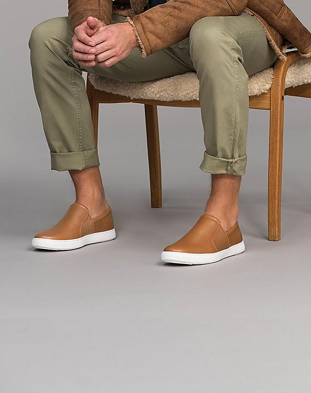 Man sitting down, wearing tan slip on shoes and khaki trousers.