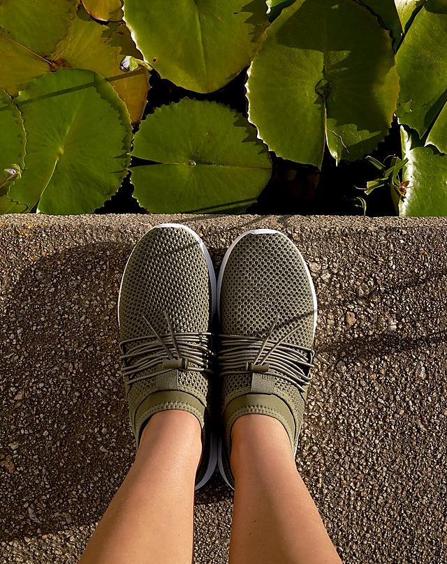 Woman wearing khaki sneakers, standing by a lily pad pond.