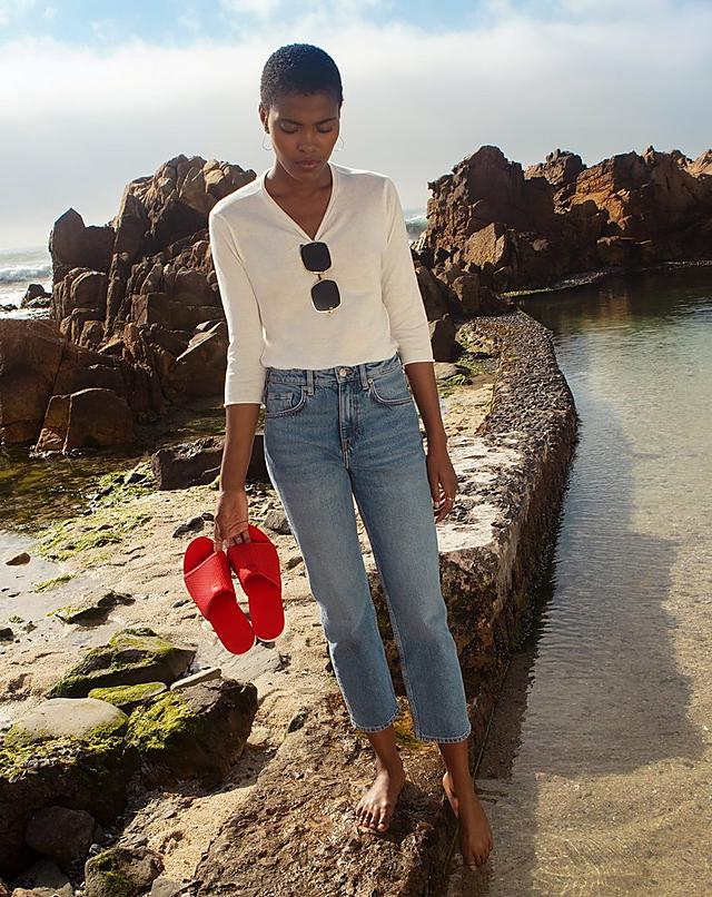 Women on beach carrying Fitflop Airmesh Red Pool Slide Sandals.