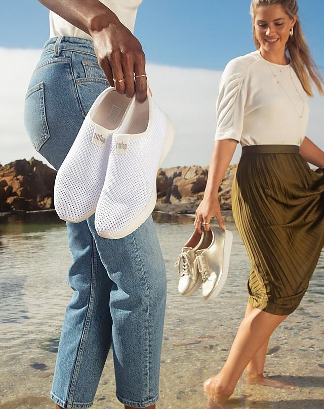 Women holding Fitflop Sneakers on Beach. Airmesh Knitted Sneakers in White and Rally Gold.