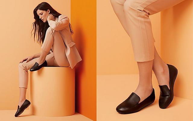 Woman wearing black loafers on an orange background.