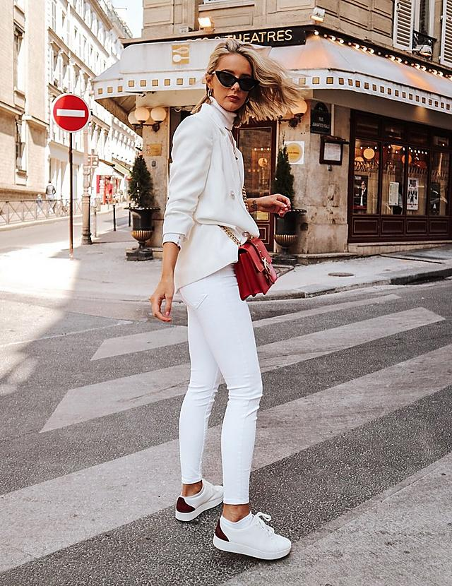 Laura Black wearing FitFlop white Rally sneakers with red Snake-print details.