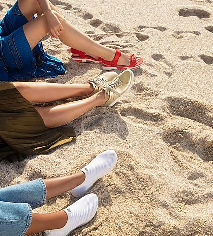 Women wearing Fitflop shoes on the beach. Red Sandals, White sneakers and Gold Sneakers.