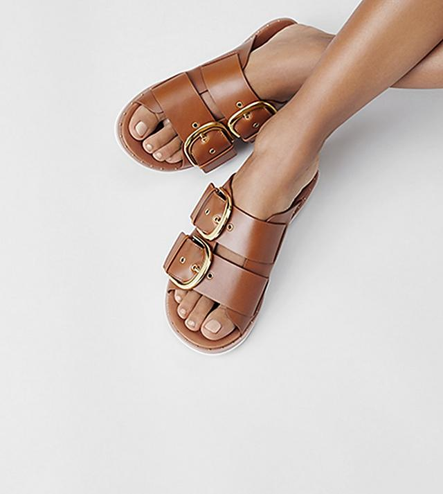 Fitflop leather buckleup slip-on sandals with two wide straps with gold buckles.