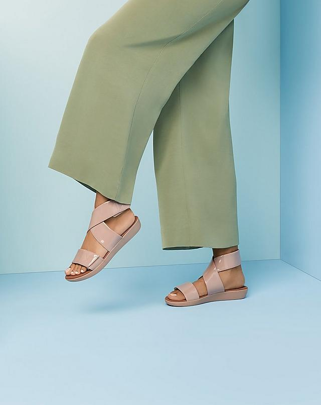 Fitflop glossy patent slide sandals with two thick straps and streamlined fastenings.