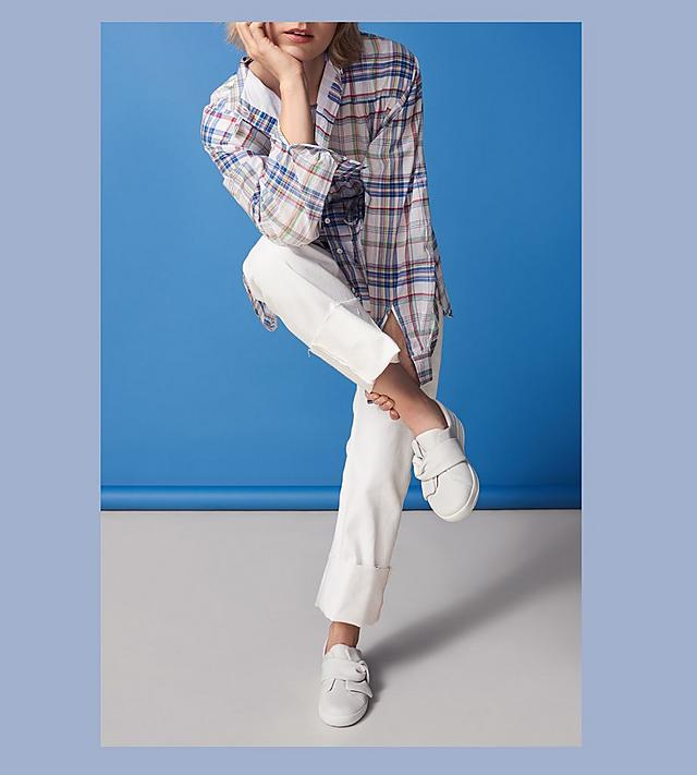 Model shot of Bowy Leather Slip-on Sneakers in white matched with white pants and a plaid shirt.