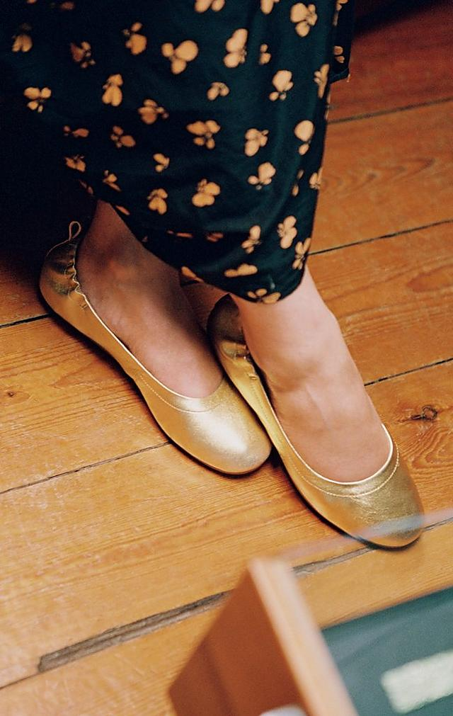 Woman wearing a black floral dress is modelling ballerina shoes in gold.