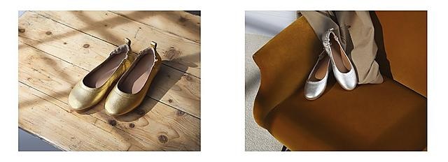 Gold ballerina shoes are placed on a wooden floor and Silver ballerina shoes are placed on the corner of a tan chair.