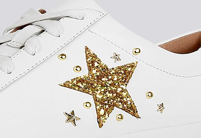 Close-up image of white leather Tennis style sneakers with gold embellished star print on the side.