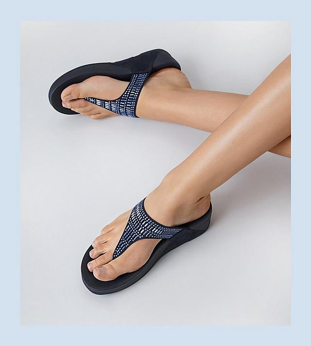 Woman wearing blue toe post sandals.