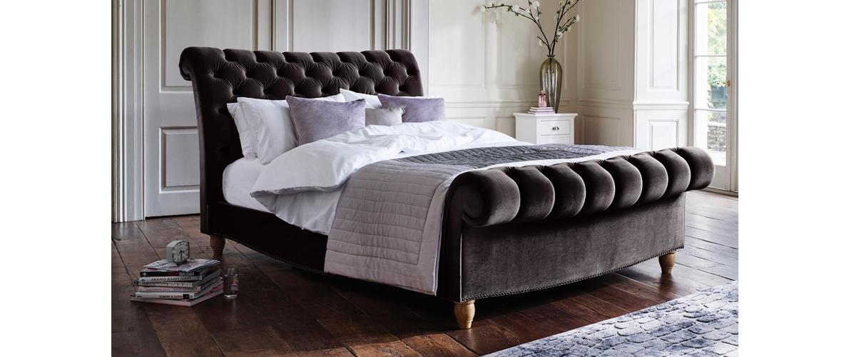 Aurora buttoned and scrolled velvet bed frame.