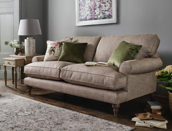 Beige sofa, velvet and floral cushions