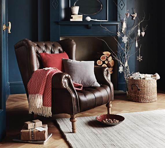 Wing back buttoned leather armchair by fireplace