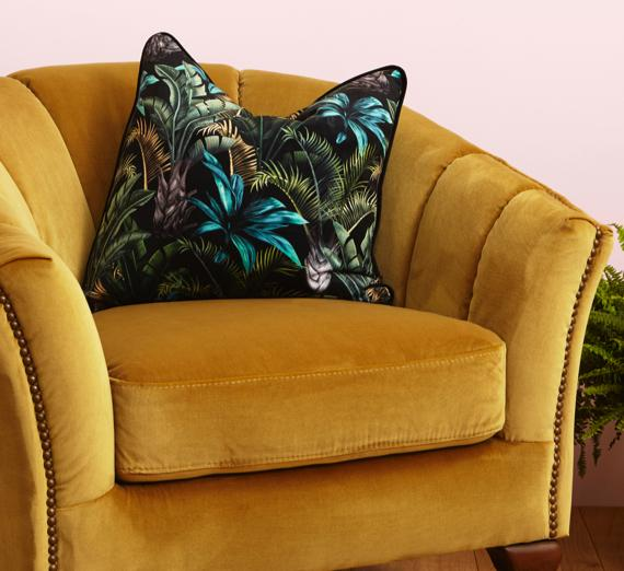 Botanical pattern cushion on yellow velvet chair.