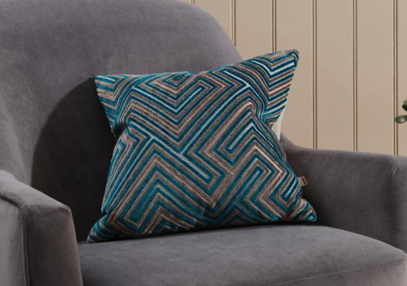 Geometric teal and taupe cushion in grey bedroom