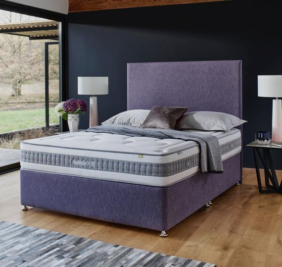 Bed with modern purple headboard in a grey bedroom