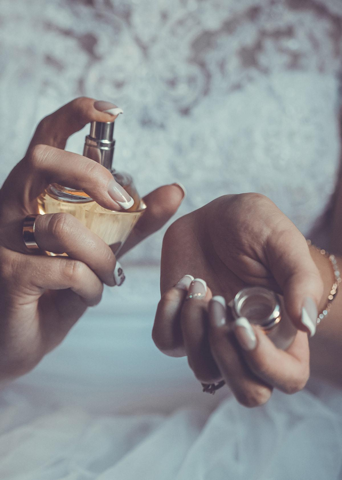 Bride spraying perfume whilst wearing jewellery