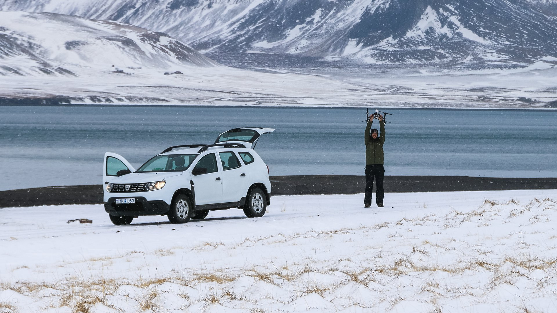 Dan Stood Holding Up Drone Next to Car in Icy Environment