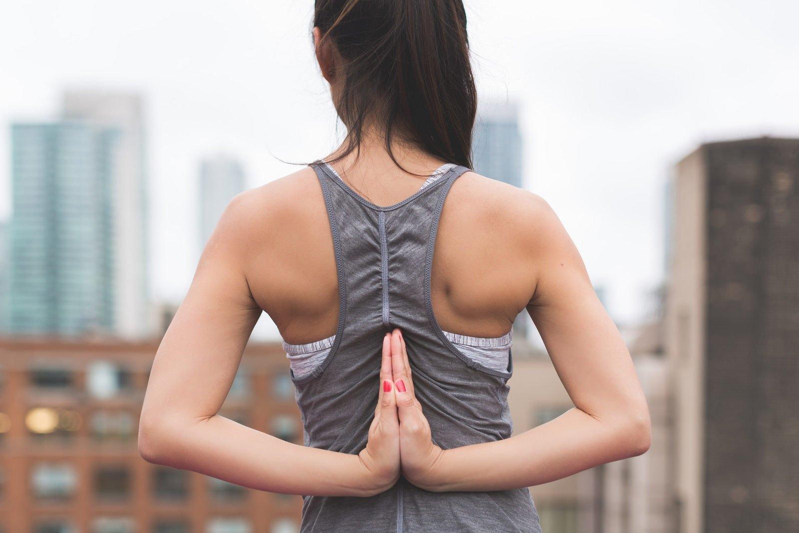 Rücken von Frau in Tanktop in Yoga Position