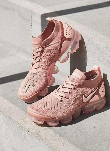 På billedet ses et par lyserøde Nike Air Vapormax sneakers. Skoene er placeret på et trappetrin af beton. Den højre sneaker er stillet op af trappetrinnet, mens den venstre står fladt på trappen. En skygge fra en lygtepæl falder i baggrunden.
