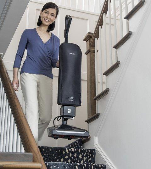 person carries Elevate vacuum up a flight of stairs