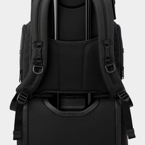 Detail of backpack securely strapped over luggage handle.