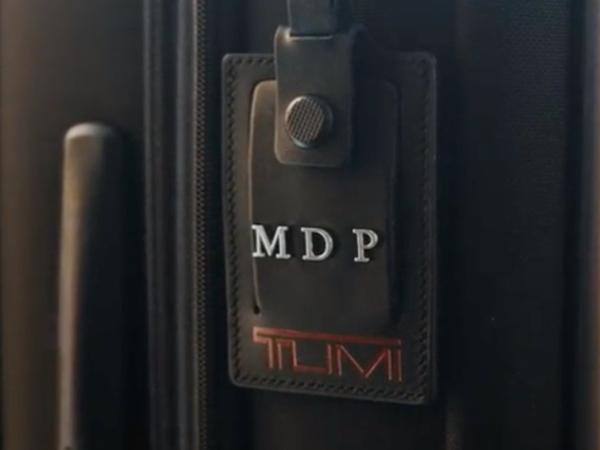 Detail of a luggage tag with monogrammed personalization initial letters.